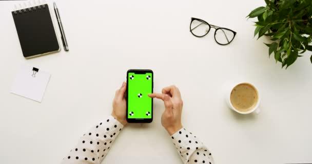 Szemközti nézet az íróasztal és a fekete smartphone-val a zöld képernyő és a női kéz szalagra rajta. Függőleges. Irodai cucc, és a kávé mellett. Chroma-kulcs. Mozgás követése