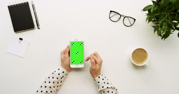 Pohled shora na úřad stůl a bílý smartphone s zeleným plátnem a ženských rukou, nahrávat na něm. Svisle. Materska a kávy vedle. Chromatický klíč. Sledování pohybu