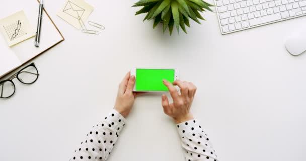 A a fehér irodai íróasztal-fehér smartphone-val a zöld képernyő és a női kéz szalagra, felülnézet. Vízszintes. Irodai cuccot mellett. Chroma-kulcs.