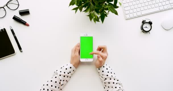 Pohled shora na bílé úřadu stůl a bílý smartphone s zeleným plátnem a ženských rukou, nahrávat na něm. Svisle. Materska vedle. Chroma klíč