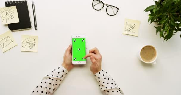 A a Hivatal pult és fehér smartphone-val zöld képernyő és a női kéz szalagra, felülnézet. Függőleges. Irodai cucc, és a kávé mellett. Chroma-kulcs. Mozgás követése