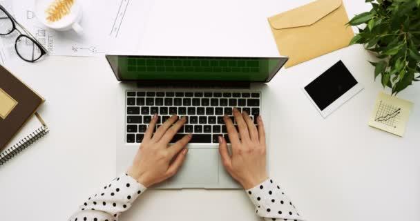 Draufsicht auf den Bürotisch mit Laptop-Computer mit grünem Bildschirm und aufgeklebten Frauenhänden. Bürokram daneben. Chroma-Schlüssel.