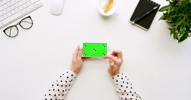 A a fehér irodai íróasztal-fehér smartphone-val a zöld képernyő és a női kéz szalagra, felülnézet. Vízszintes. Irodai cuccot mellett. Chroma-kulcs. Ttracking mozgás