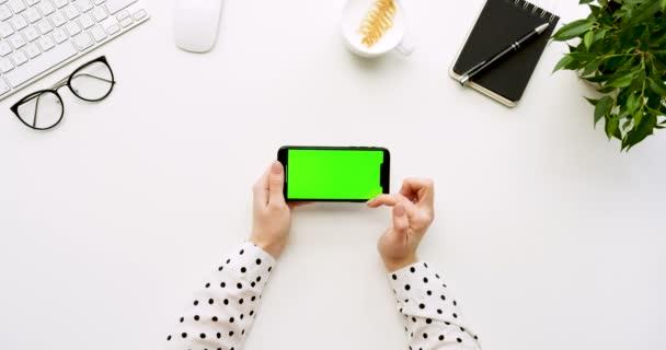 Felülnézet, fehér íróasztal és fekete smartphone-val a zöld képernyő és a női kéz szalagra rajta. Vízszintes. Irodai cuccot mellett. Chroma-kulcs.