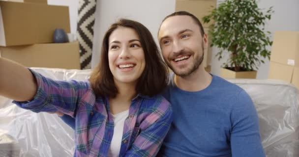 junges glückliches kaukasisches Paar, das an einem einziehenden Tag schöne und lustige Selfies auf der Couch zwischen Kisten und Sachen macht. Neue Heimat. Nahaufnahme. Innenräume