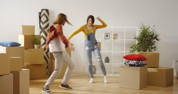 Ein junges, fröhliches Ehepaar, das sich beim Einzug in die neue Wohnung im Wohnzimmer zwischen gepackten Kartons und Hausrat vergnügt, hüpft und dreht. Innen