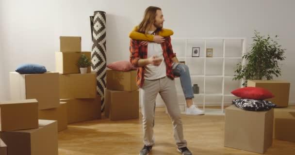 junge kaukasische attraktive Freund und Freundin Spaß haben und glücklich sein in ihrer neuen Wohnung zwischen ausgepackten Kisten beim Einzug t.otogether inside