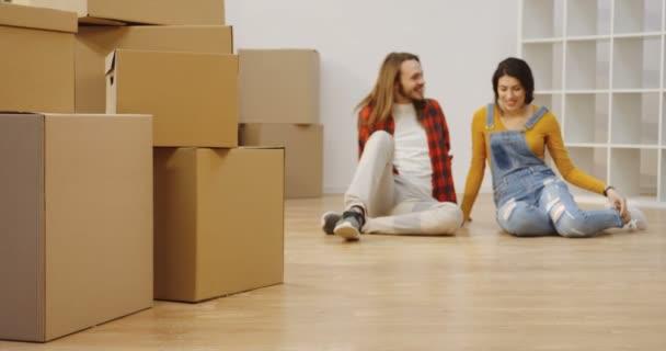 Viele Kisten vor der Kamera und ein sprechendes junges Paar auf dem verschwommenen Hintergrund in der Wohnung. Junge Leute ziehen gemeinsam ein. Innenräume