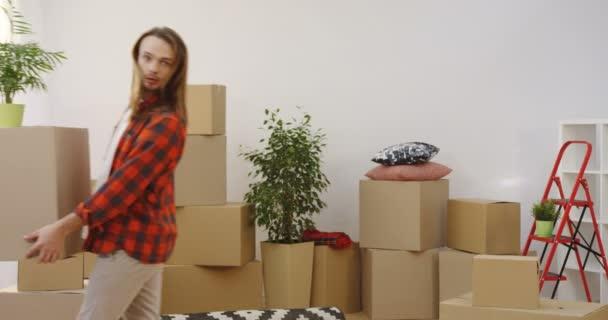 Fiatal házasok pár él együtt, és otthon dolgokat eltávolítása a nappaliban. Beltéri