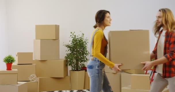 Leere Zimmer mit ausgepackten Kisten und Hausrat und ein junges nettes Paar, das eine Schachtel hin- und herträgt. Innenräume