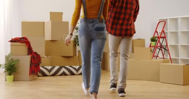 Rückansicht des jungen attraktiven Paares, das am Tag des Einzugs lächelnd die neue gemütliche Wohnung betritt und sich zwischen ausgepackten Kartons und Hausrat im Wohnzimmer der Kamera zuwendet. Innen