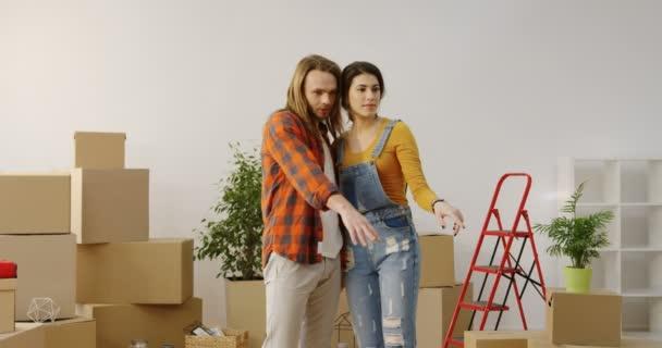 Just married junge schöne Paar stehend in der Mitte das Wohnzimmer umgeben von Kisten ausgepackt und Planung der Gestaltung der Wohnung. Im Inneren