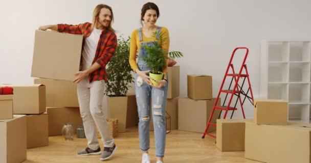 junges kaukasisches Ehepaar, das zusammen in das neue Haus einzieht und eine gepackte Schachtel und Pflanze in einem Topf mit vielen Schachteln und Hausrat ins Wohnzimmer bringt. drinnen
