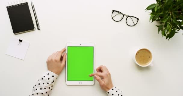 Pohled shora na kancelářský stůl a bílé tabletový počítač s zeleným plátnem a ženských rukou, nahrávat na něm. Svisle. Materska a kávy vedle. Chroma klíč