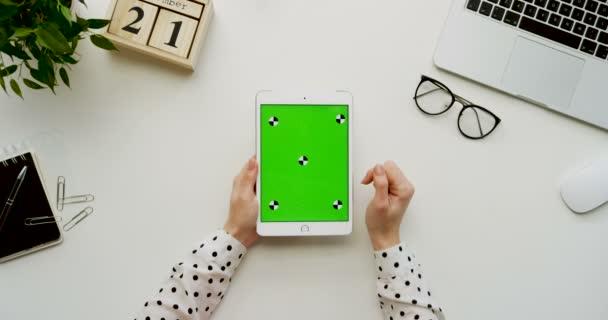 Pohled shora na kancelářský stůl a bílé tabletový počítač s zeleným plátnem a ženských rukou, nahrávat na něm. Svisle. Materska vedle. Chromatický klíč. Sledování pohybu