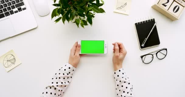 Pohled shora na úřad stůl a bílý smartphone s zeleným plátnem a ženských rukou, nahrávat na něm. Vodorovně. Materska vedle. Chroma klíč