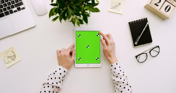 Draufsicht auf den Schreibtisch und weiße Tablet-Computer mit Greenscreen und weibliche Hände Abkleben auf es. Vertikale. Büro-Zeug neben. Chroma-Key. Verfolgen von Bewegung