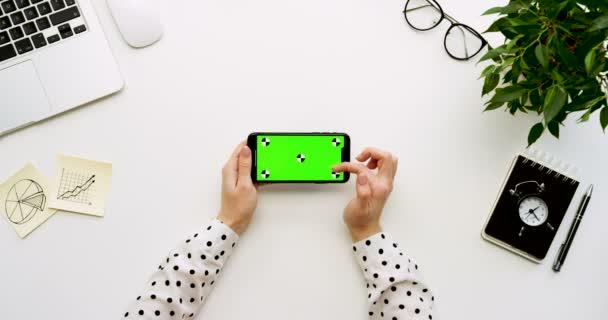Pohled shora na kancelářský stůl a černý smartphone s zeleným plátnem a ženských rukou, nahrávat na něm. Vodorovně. Materska vedle. Chromatický klíč. Sledování pohybu