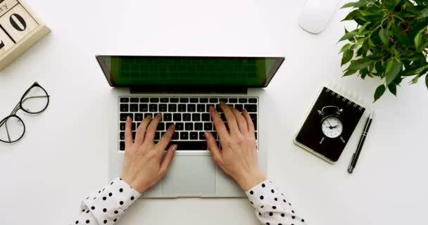 Pohled shora na tabulce úřadu s přenosný počítač s zeleným plátnem a ženských rukou, nahrávat na něm. Poznámkové bloky vedle. Chroma klíč