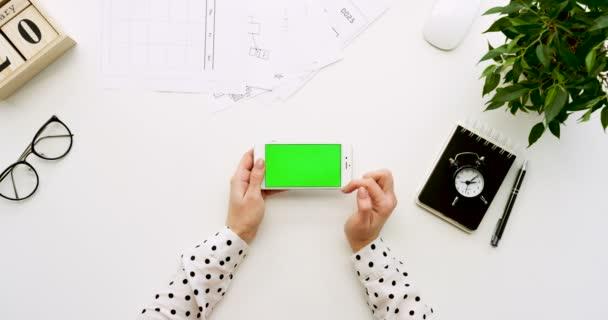 A a Hivatal pult és fehér smartphone-val zöld képernyő és a női kéz szalagra, felülnézet. Vízszintes. Irodai cuccot mellett. Chroma-kulcs.