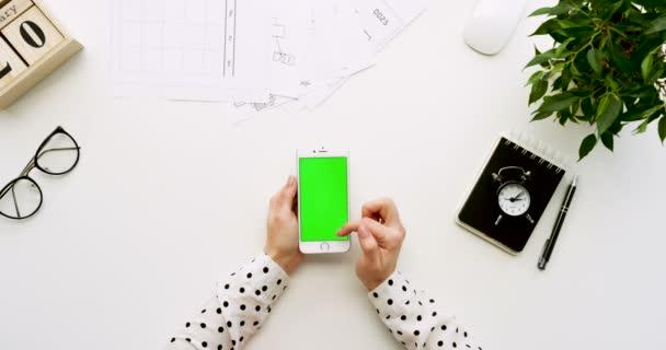 A a Hivatal pult és fehér smartphone-val zöld képernyő és a női kéz szalagra, felülnézet. Függőleges. Irodai cuccot mellett. Chroma-kulcs.