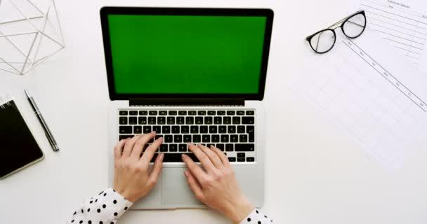 Pohled shora na tabulce úřadu s přenosný počítač s zeleným plátnem a ženských rukou, nahrávat na něm. Poznámkové bloky a brýle vedle. Chroma klíč