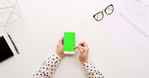 Pohled shora na úřad stůl a bílý smartphone s zeleným plátnem a ženských rukou, nahrávat na něm. Svisle. Materska vedle. Chroma klíč