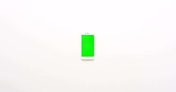 Pohled shora na prázdné bílé office tabulka a bílý smartphone s zeleným plátnem. Chromatický klíč. Vertikální