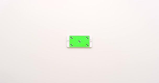 Pohled shora na prázdné bílé office tabulka a bílý smartphone s zeleným plátnem. Chromatický klíč. Vodorovně. Sledování pohybu