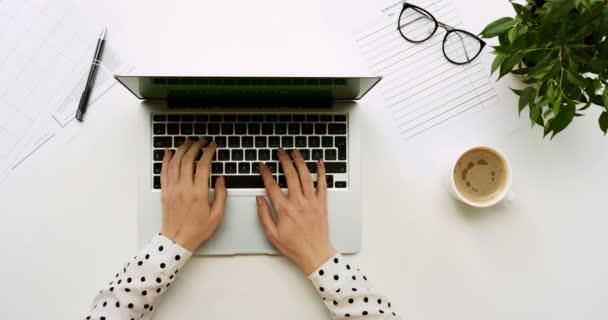 Pohled shora na tabulce úřadu s přenosný počítač s zeleným plátnem a ženských rukou, nahrávat na něm. Brýle, pero a kávy vedle. Chroma klíč