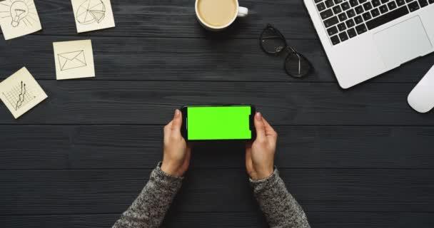 Felülnézet fekete íróasztal és fekete smartphone-val a zöld képernyő és a női kéz szalagra rajta. Vízszintes. Irodai cucc, a laptop és a kávé mellett. Chroma-kulcs.