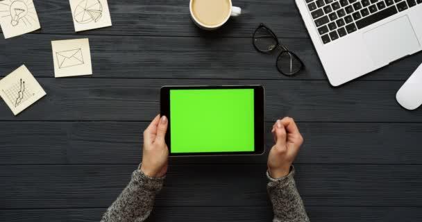 Pohled shora na černé v kanceláři a černou tabletový počítač s zeleným plátnem a ženských rukou, nahrávat na něm. Vodorovně. Kancelářské vybavení, laptop a kávy vedle. Chroma klíč