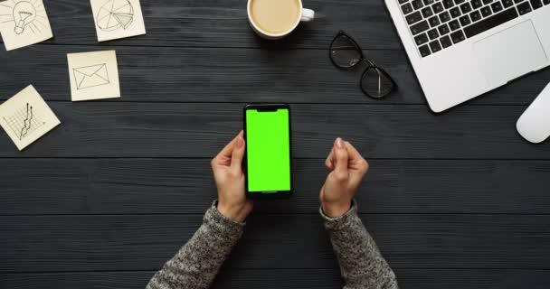Felülnézet fekete íróasztal és fekete smartphone-val a zöld képernyő és a női kéz szalagra rajta. Függőleges. Irodai cucc, a laptop és a kávé mellett. Chroma-kulcs.