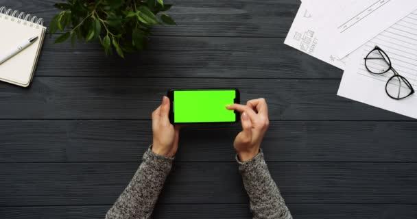 Felülnézet fekete íróasztal és fekete smartphone-val a zöld képernyő és a női kéz szalagra rajta. Vízszintes. Irodai cuccot mellett. Chroma-kulcs.