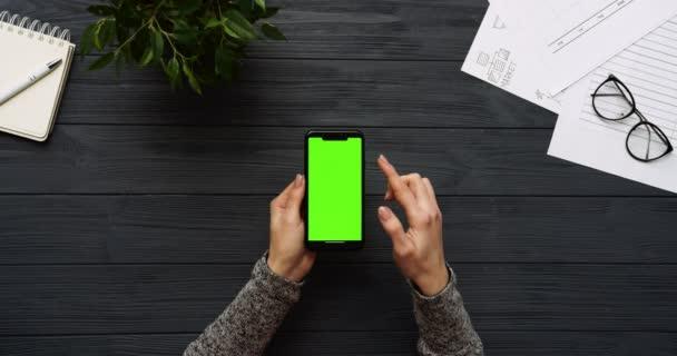 Pohled shora na černé v kanceláři a černý smartphone s zeleným plátnem a ženských rukou, nahrávat na něm. Svisle. Materska vedle. Chroma klíč