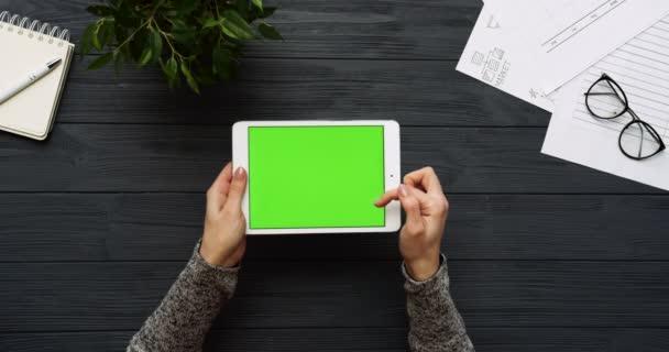 Pohled shora na černé kancelářský stůl a bílé tabletový počítač s zeleným plátnem a ženských rukou, nahrávat na něm. Vodorovně. Materska vedle. Chroma klíč