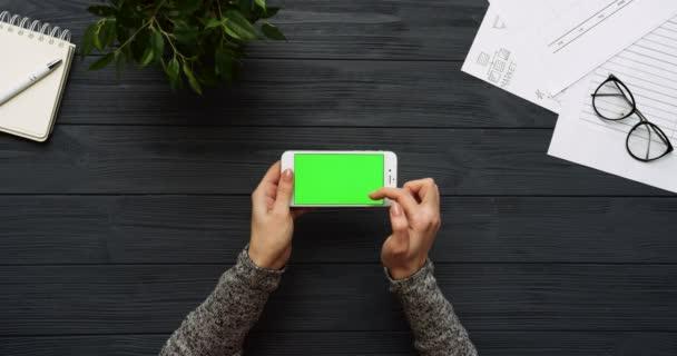 Szemközti nézet a fekete irodai íróasztal-fehér smartphone zöld képernyő és a női kéz a szalagra. Vízszintes. Irodai cuccot mellett. Chroma-kulcs.