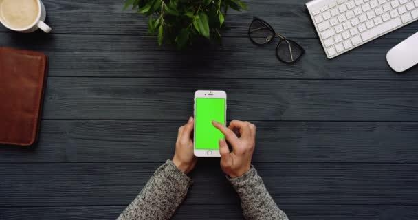 Szemközti nézet a fekete irodai íróasztal-fehér smartphone zöld képernyő és a női kéz a szalagra. Függőleges. Irodai cuccot mellett. Chroma-kulcs.