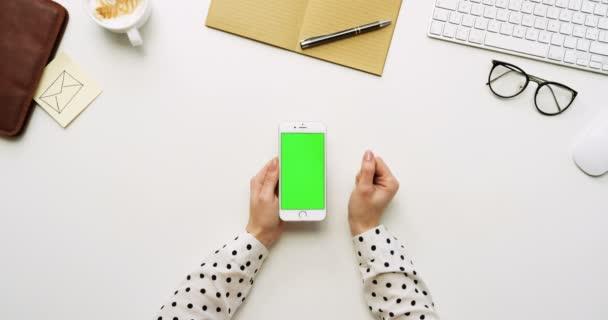 A a fehér irodai íróasztal-fehér smartphone-val a zöld képernyő és a női kéz szalagra, felülnézet. Függőleges. Irodai cuccot mellett. Chroma-kulcs.