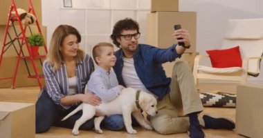 Happy Caucasian family sitting on the floor with a little labrador puppy and doing selfies surrounded by unpacked boxes in their new home. Indoors