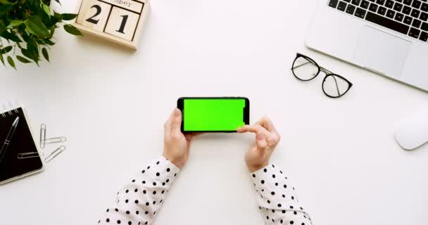 Felülnézet, fehér íróasztal és fekete smartphone-val a zöld képernyő és a női kéz szalagra rajta. Vízszintes. Irodai cucc, a laptop és a szemüveg mellett. Chroma-kulcs.