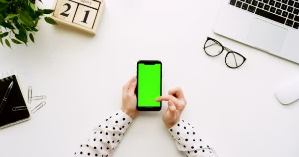 Felülnézet, fehér íróasztal és fekete smartphone-val a zöld képernyő és a női kéz szalagra rajta. Függőleges. Irodai cucc, a laptop és a szemüveg mellett. Chroma-kulcs.
