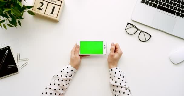 A a fehér irodai íróasztal-fehér smartphone-val a zöld képernyő és a női kéz szalagra, felülnézet. Vízszintes. Irodai cucc, a laptop és a szemüveg mellett. Chroma-kulcs.