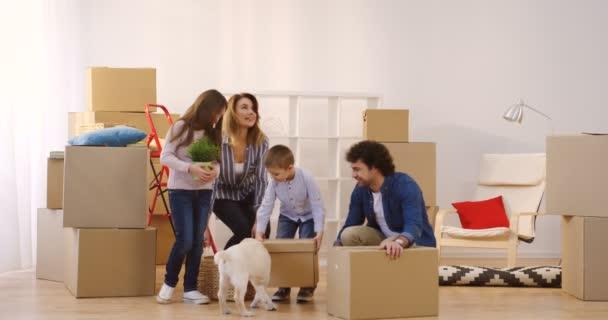 Pohybující se v novém domově šťastné rodiče s dcerou a synem a štěně labrador pes. Rozbalování krabice a Bavíte se spolu. Uvnitř