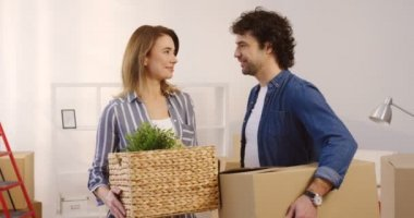 Portrait of the married middle aged woman and man looking at each other and then smiling to the camera while moving in the new flat and holding plant and box in hands. Inside. Close up.