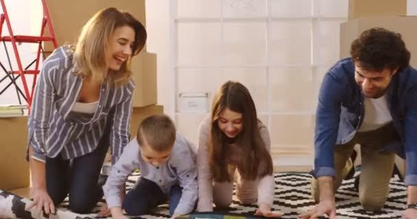 Eine glückliche Familie aus Eltern und zwei Kindern, die beim Einzug in das neue Zuhause den Teppich im Wohnzimmer zwischen gepackten Kisten ausrollen. drinnen