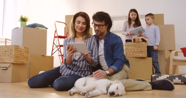 Attractive married man and woman sitting on the floor with their labrador dog and sxrolling on the tablet device while their kids playing behind. Moving in the new home. Inside