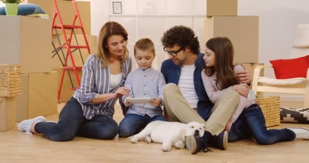 Pěkný krásný rodina sedí na podlaze mezi boxy s domácí věci a sledování něco na obrazovku tabletu, zatímco jejich pes spí vedle. Portrét shot. Uvnitř
