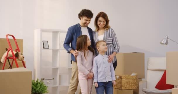 Porträt gedreht von den glücklichen Eltern mit Kindern stehen im gemütlichen Wohnzimmer voller Kisten ausgepackt und posiert mit Schlüssel aus einem neuen Haus. Im Innenbereich