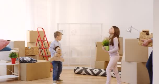 Happy family coming in the new cozy apartment and bringing carton boxes and home stuff there as moving in it. Indoors